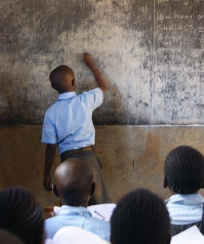 Schoolboy wriitng on blackboard in Africa